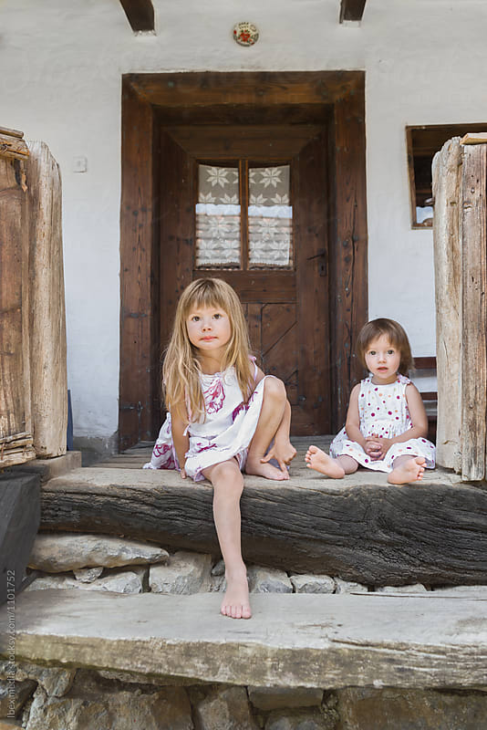 Little girls sitting down on stairs in front of traditional home by RG&B Images for Stocksy United
