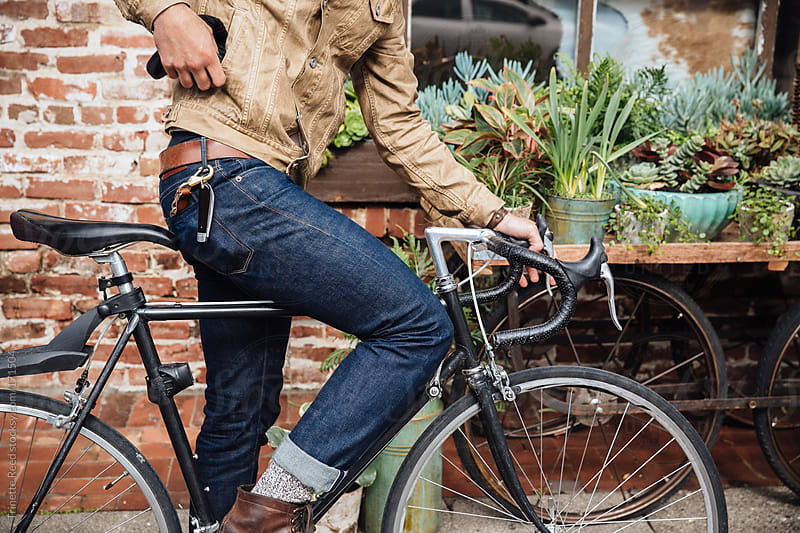 Hipster millennial on bike in urban area by Trinette Reed for Stocksy United