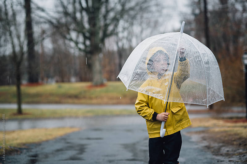 little boy outside in yellow coat with umbrella by Léa Jones for Stocksy United