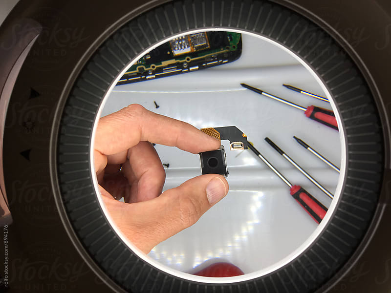 Man's hand holding object under magnifying lens by rolfo for Stocksy United