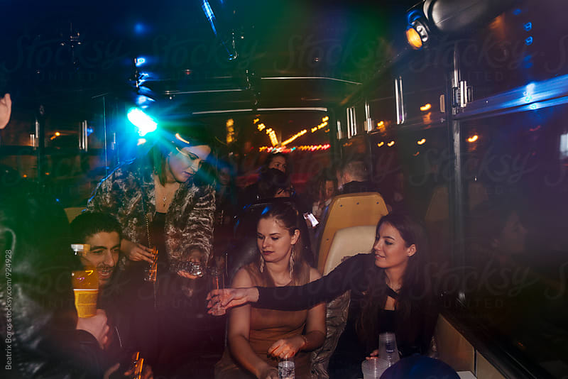 People having fun in party bus by Beatrix Boros for Stocksy United
