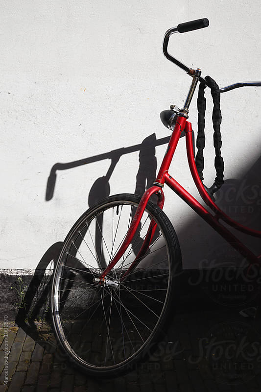 Red bike and shadow by Marcel for Stocksy United