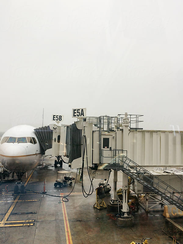 Plane sitting at a jetway in the rain. by Lucas Saugen for Stocksy United
