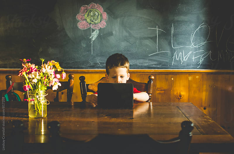 Child playing on electronic device at a table by Lindsay Crandall for Stocksy United