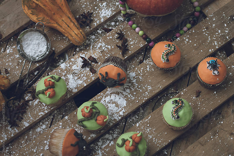 Halloween theme decorated cupcakes with powdered sugar sprinkled on table  by Beatrix Boros for Stocksy United