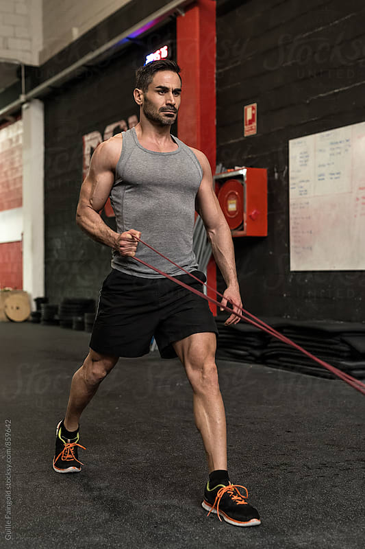 Man working out with resistance bands in  gym by Guille Faingold for Stocksy United