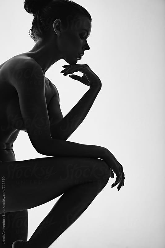 Beautiful silhouette of nude woman thinking with her hand on chin by Jacob Lund for Stocksy United