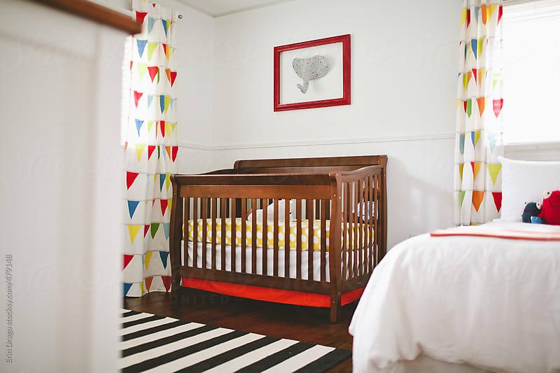 newborn in crib in nursery by Erin Drago for Stocksy United