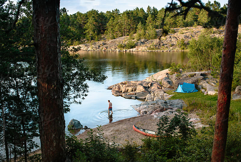 Men is going for a swim in front of his tent  in nature by Denni Van Huis for Stocksy United