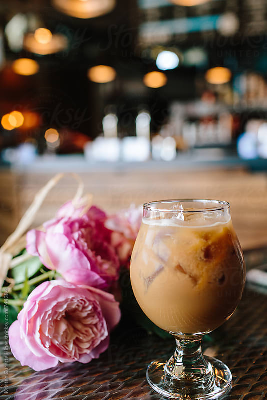 Fancy Iced Coffee with cream in a Glass beside pink flowers by Kristen Curette Hines for Stocksy United
