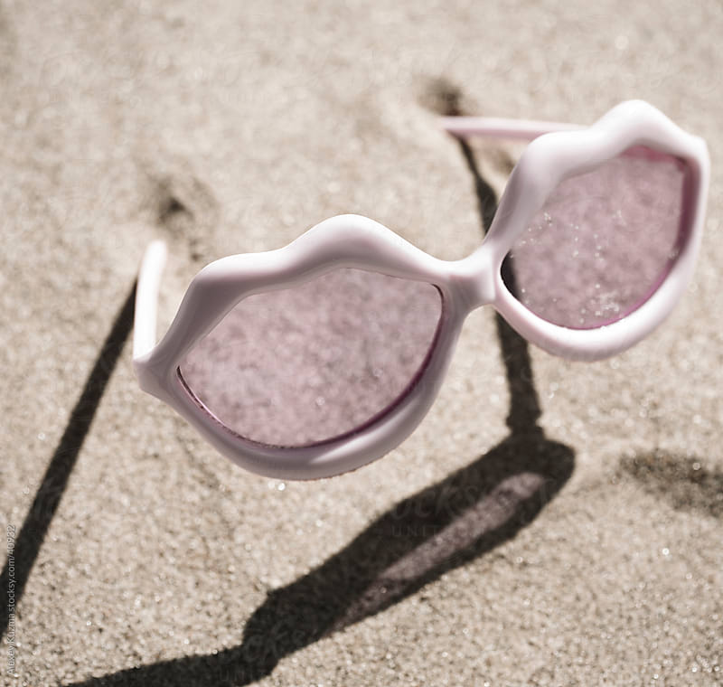 lips-shaped glasses on the sand by Alexey Kuzma for Stocksy United