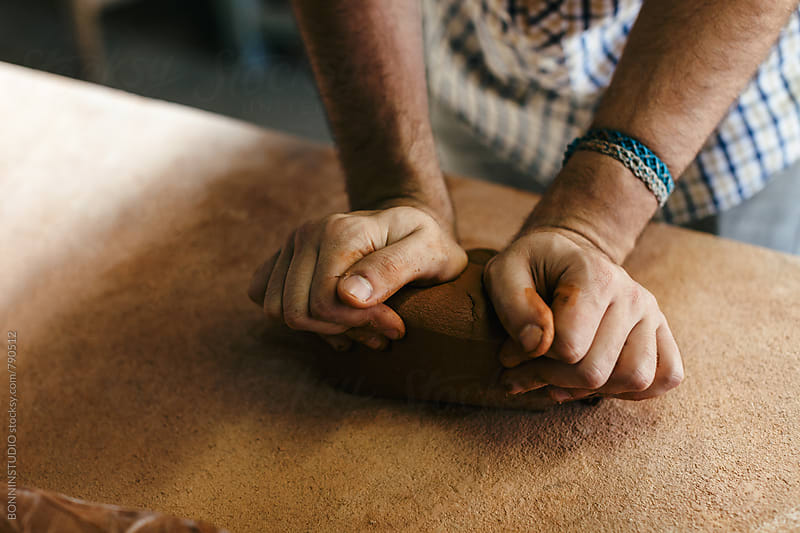 Hands of a ceramist working with clay in a workspace. by BONNINSTUDIO for Stocksy United