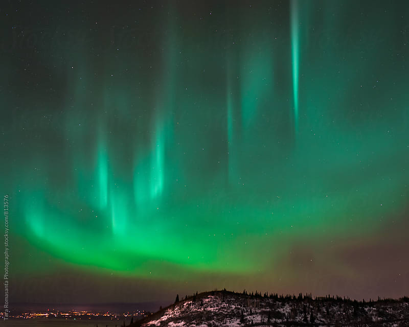 aurora borealis with city lights in the distance by Tara Romasanta for Stocksy United