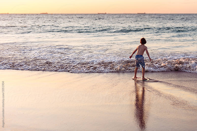 Boy skimming on a board at the beach at sunset by Angela Lumsden for Stocksy United