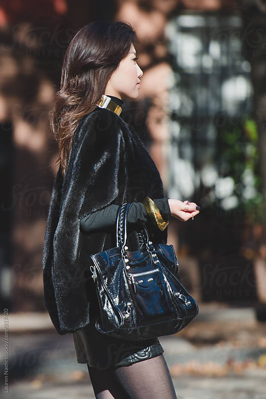 Elegant young woman walking down the street by Lauren Naefe for Stocksy United