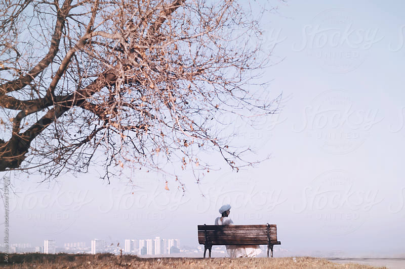 Girl sitting on a park bench  by Jovana Rikalo for Stocksy United