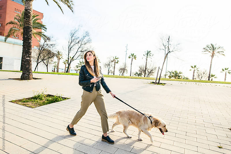 Young woman walking her dog on sidewalk using phone. by BONNINSTUDIO for Stocksy United
