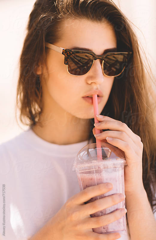 young woman with vintage sunglasses and fresh berry smoothie by Alexey Kuzma for Stocksy United