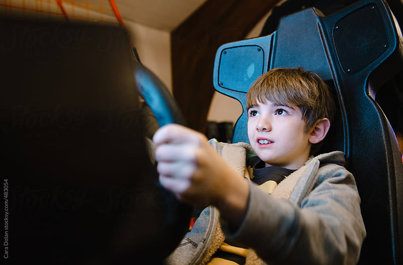 Child plays a driving video game in an arcade by Cara Dolan for Stocksy United
