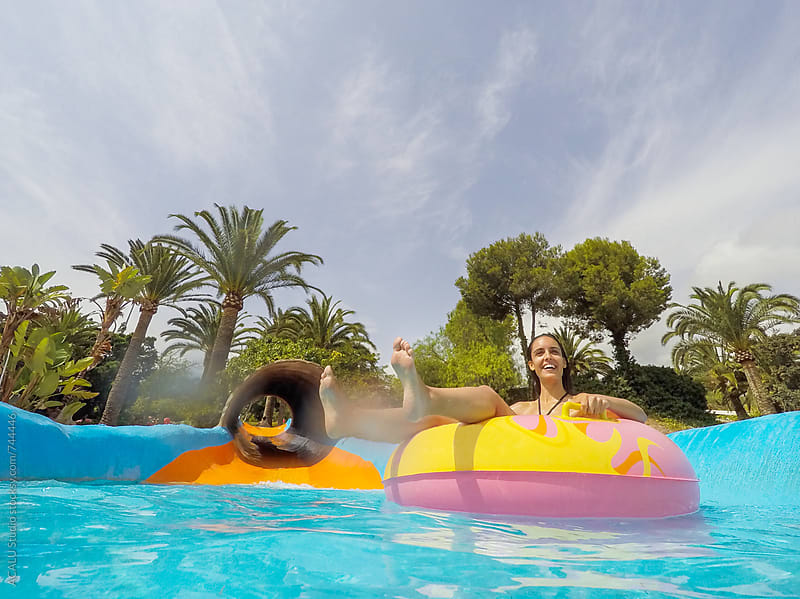 Woman with an inflatable mattress on a waterpark by ACALU Studio for Stocksy United