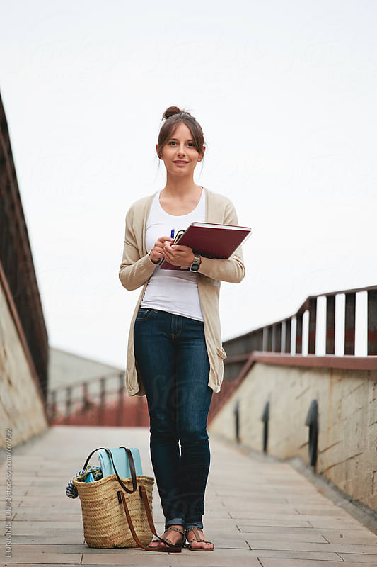 Beautiful casual young student woman standing on the street with notebook. by BONNINSTUDIO for Stocksy United
