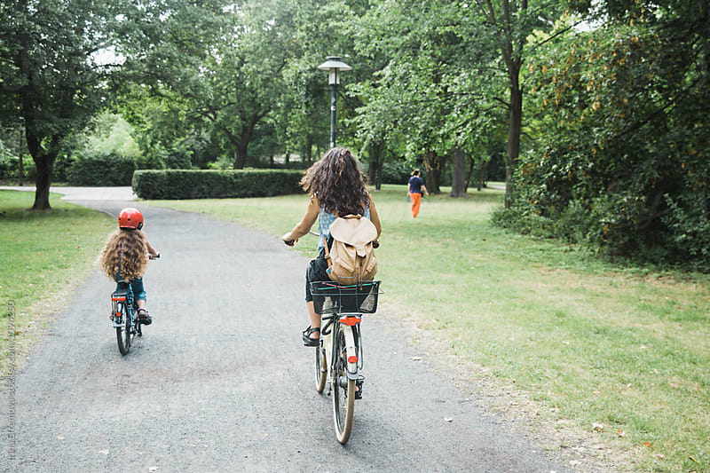 Mother and Daughter cycling through the park by Irina Efremova for Stocksy United