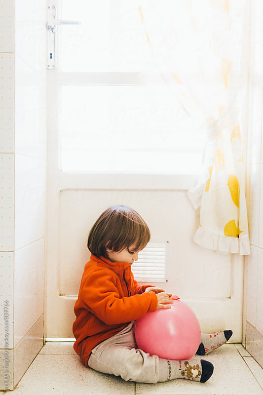Little baby sitting playing with a pink balloon by michela ravasio for Stocksy United