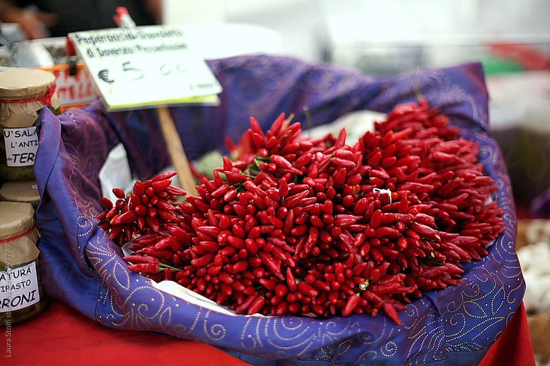 Small italian red chili peppers for sale at the market by Laura Stolfi for Stocksy United