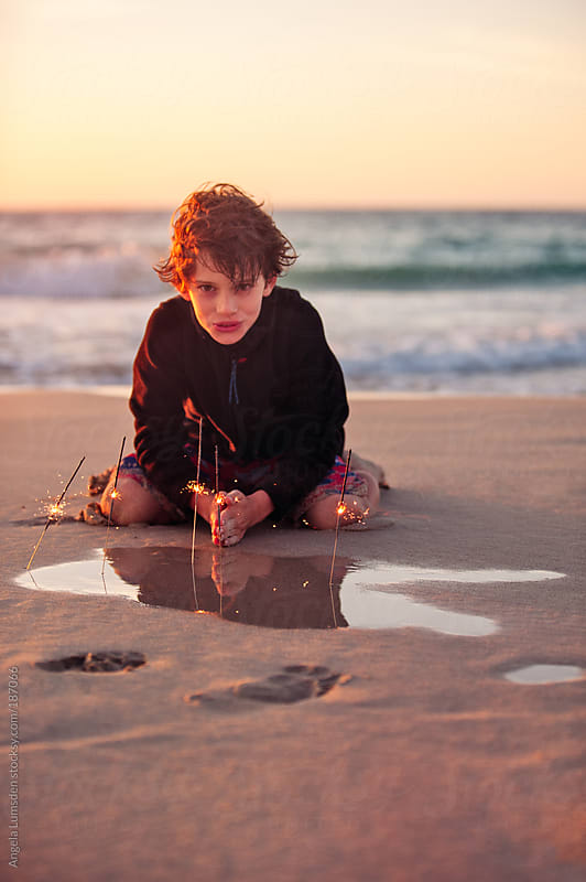 Boy playing with sparklers at the beach at sunset by Angela Lumsden for Stocksy United