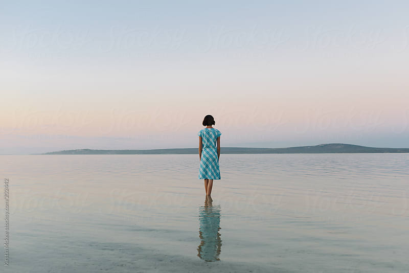 Girl standing in a lagoon at sunset by Kirstin Mckee for Stocksy United
