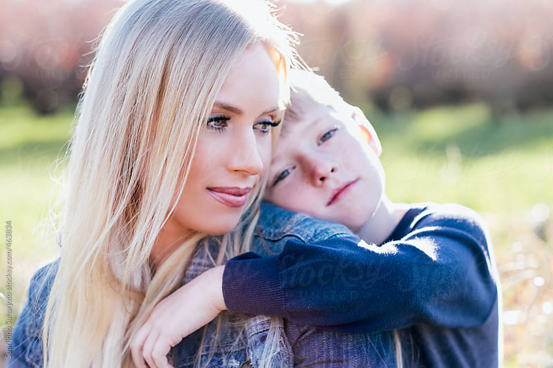 Portrait of a boy hugging his mother outdoor on a sunny day by Suprijono Suharjoto for Stocksy United
