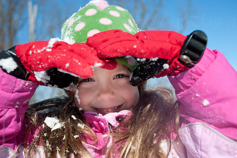 Wintry Portrait of a Happy Little Girl Playing in Snow by Brian McEntire for Stocksy United