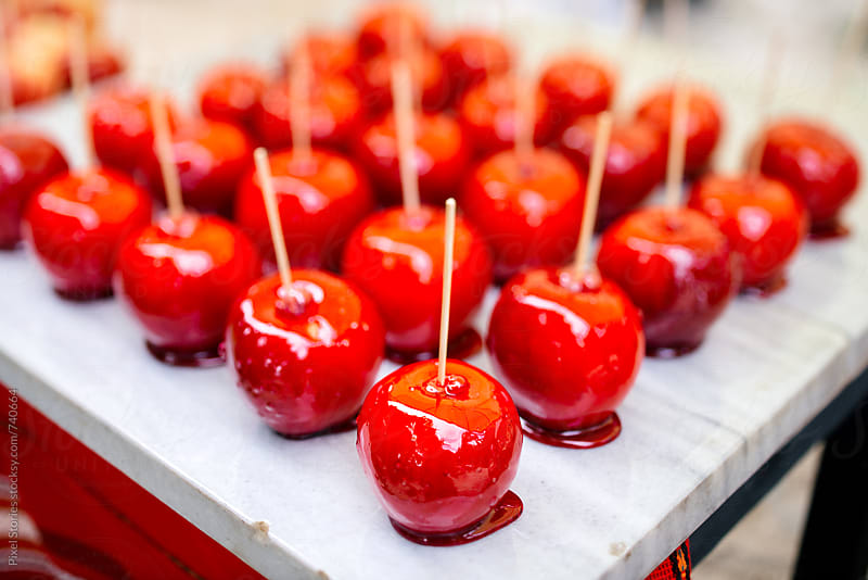 Just coated candy apples in a row for Halloween by Pixel Stories for Stocksy United