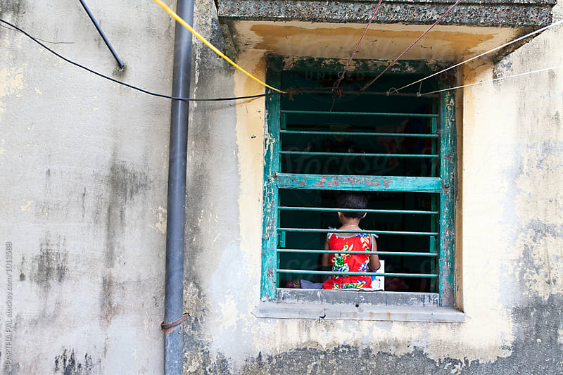 A little girl sitting behind a window,rear view by PARTHA PAL for Stocksy United