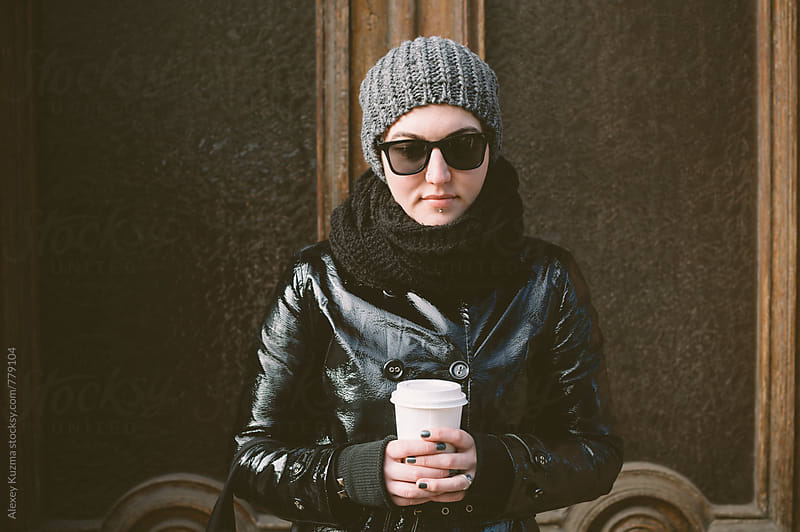 androgyne on the street with coffee  by Alexey Kuzma for Stocksy United