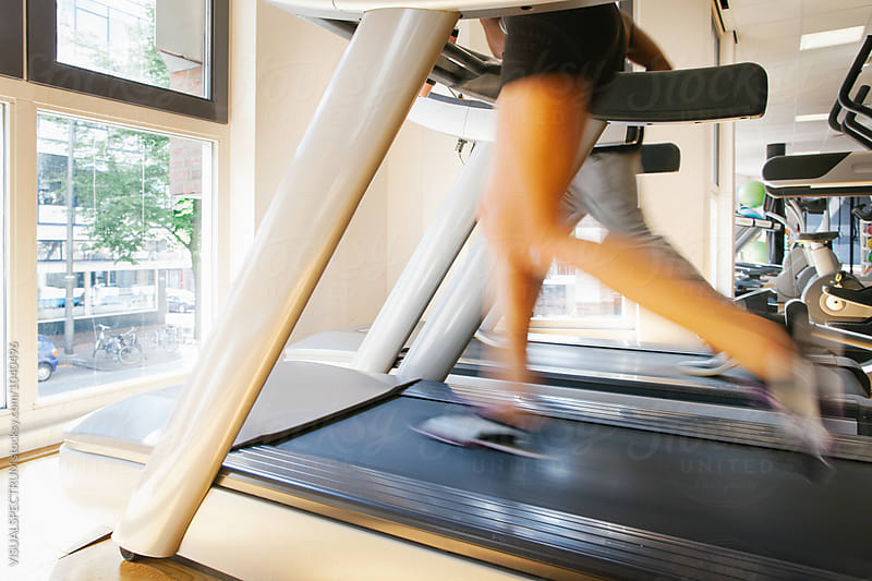 Blurred Legs of Slim Woman Running on Treadmill by VISUALSPECTRUM for Stocksy United