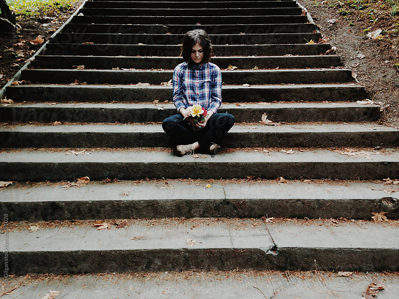 Girl sits on steps with roses by Kevin Gilgan for Stocksy United