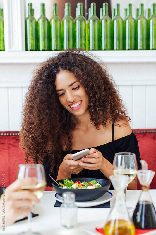 Woman using her phone whilst eating a salad in a restaurant.  by BONNINSTUDIO for Stocksy United