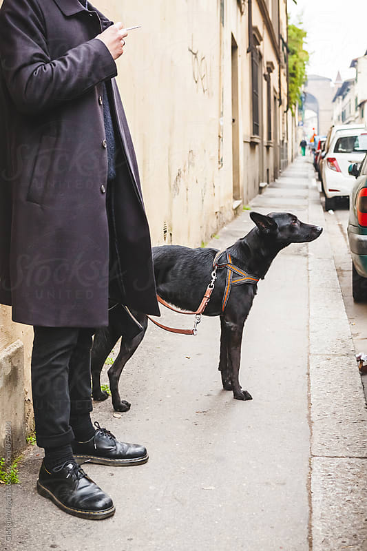 Vigilant Black Dog with Owner Standing on the Sidewalk in Italy by Giorgio Magini for Stocksy United