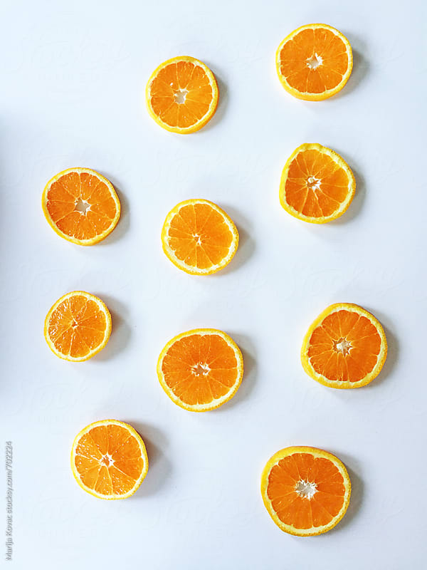 Many slices of an orange on a white background by Marija Kovac for Stocksy United