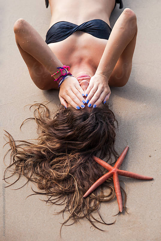 Beautiful woman at the beach with the starfish in her hair by Jovo Jovanovic for Stocksy United