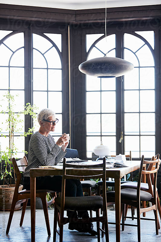 Senior Design Professional Having Coffee At Table by ALTO IMAGES for Stocksy United