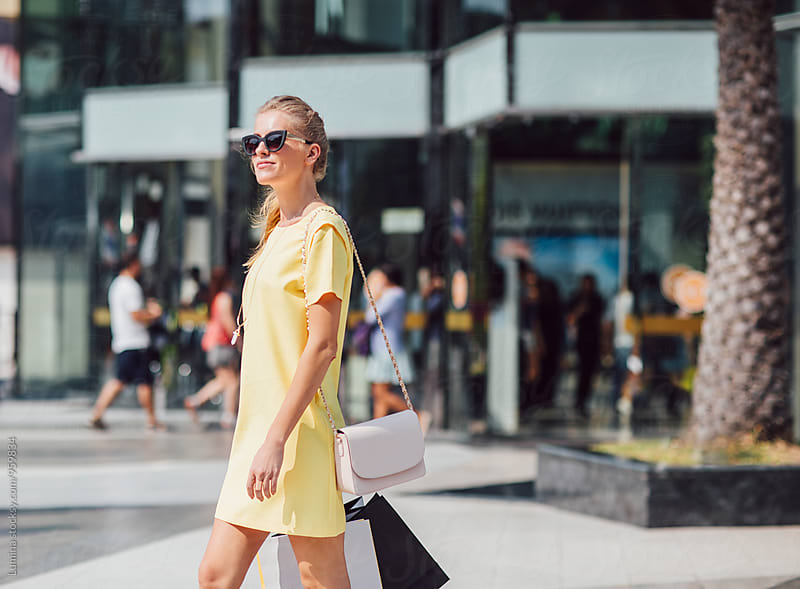 Blonde Woman Carrying Shopping Bags on the Street by Lumina for Stocksy United