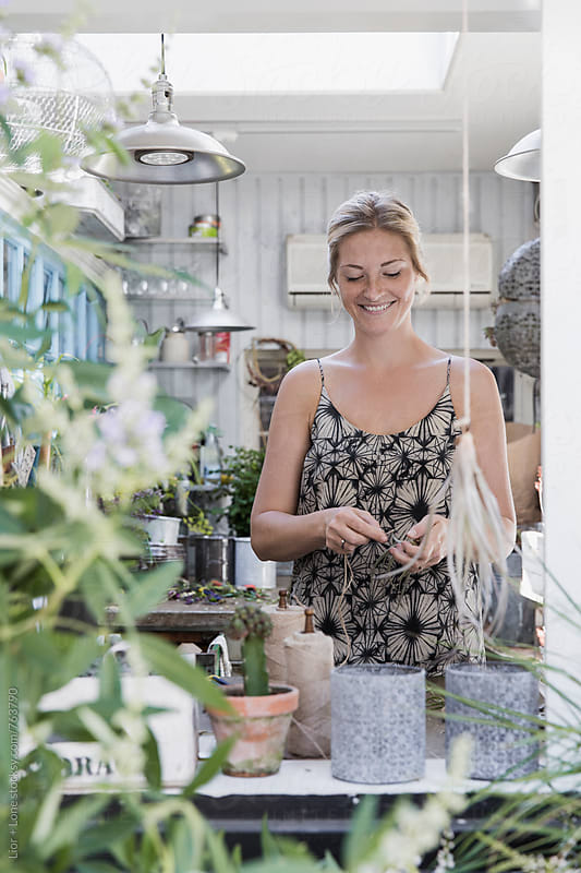 young beautiful woman smiling while working in a flower shop by Lior + Lone for Stocksy United