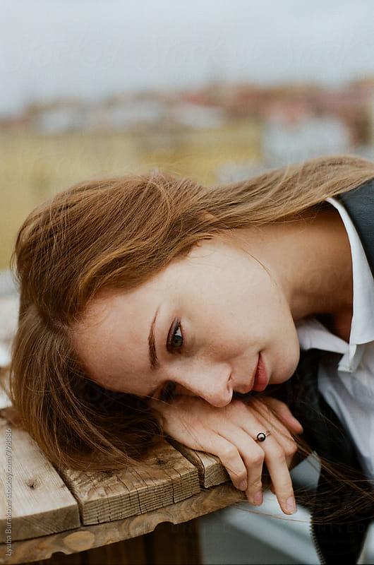 Portrait of a woman lying on her hand by Liubov Burakova for Stocksy United