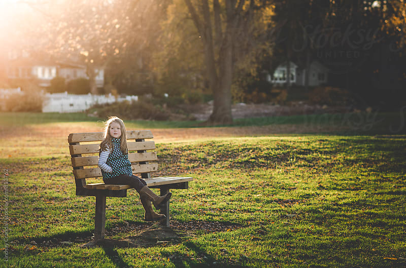 Girl sitting on a bench by Lindsay Crandall for Stocksy United