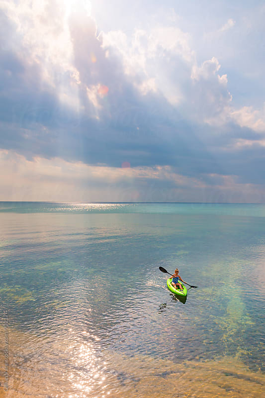 teen girl kayaking in the ocean under amazing clouds by Gillian Vann for Stocksy United