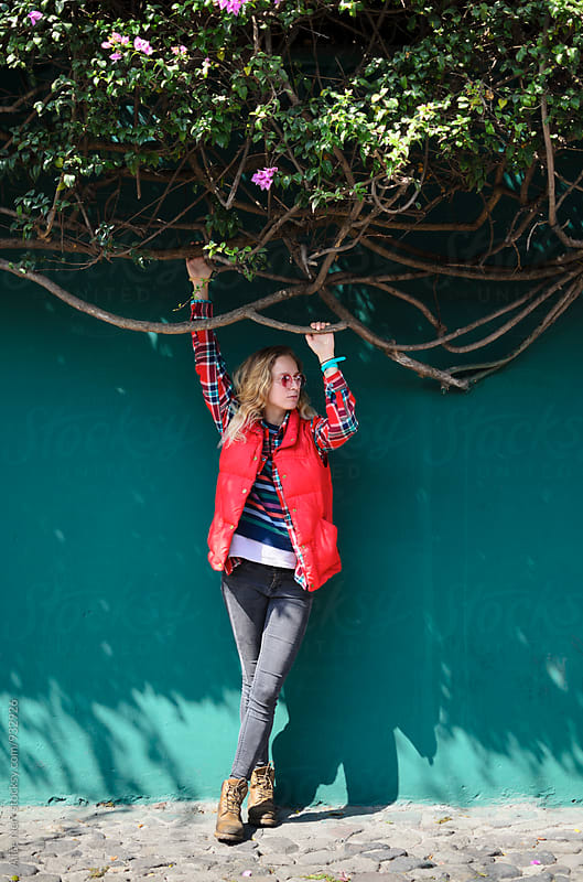 Young blond woman standing next to the green wall covered with blooming tree branches by Alice Nerr for Stocksy United