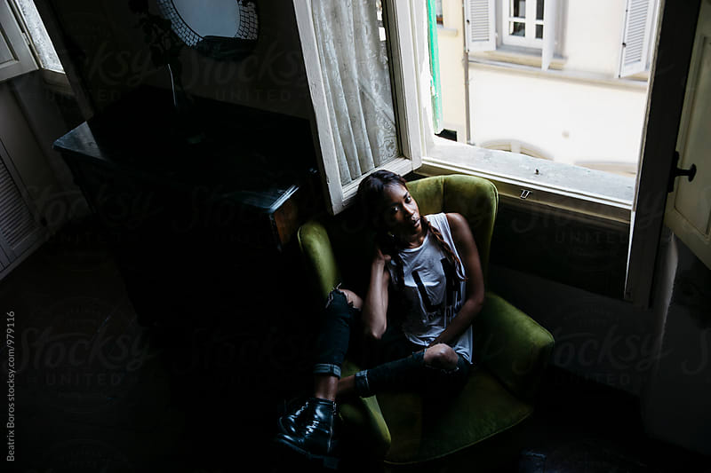 Overhead photo of a young black woman sitting in an armchair by Beatrix Boros for Stocksy United