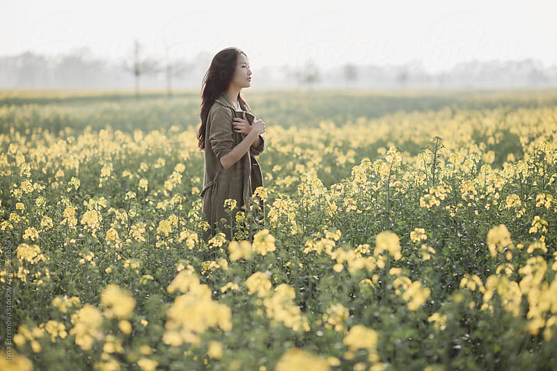 Asian girl on the yellow field by Irina Efremova for Stocksy United